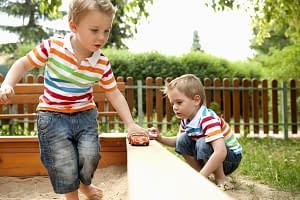 Spielende Kinder in sauberem Sand auf Spielplatz dank Spielsandreinigung durch den Sandfuchs
