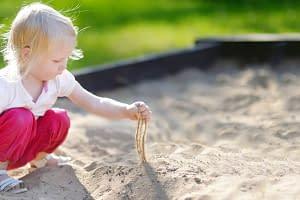 Kind spielt im gereinigten Sand von Sandfuchs