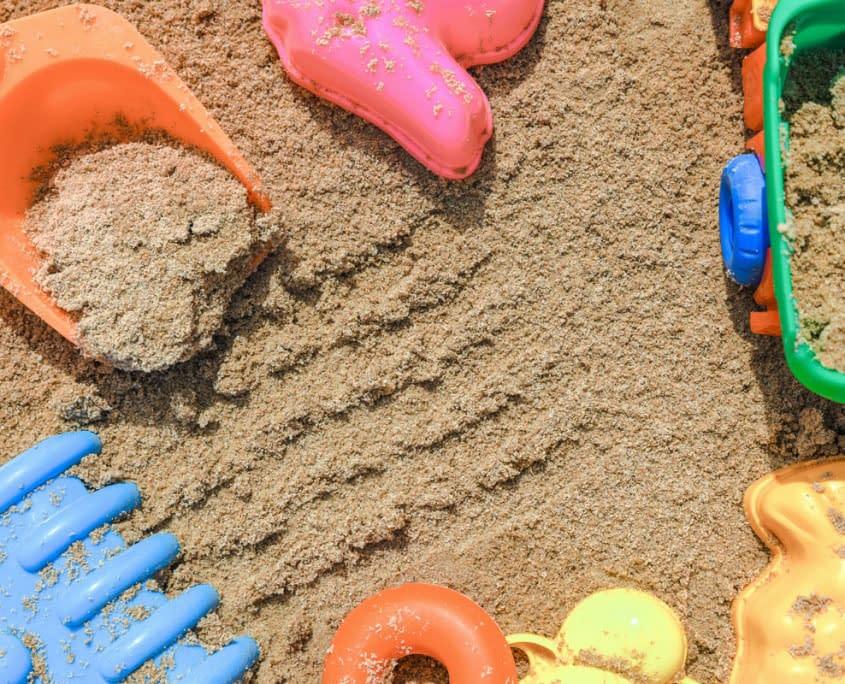 Sandspielzeug in sauberem Sand auf Spielplatz dank Spielsandreinigung durch den Sandfuchs